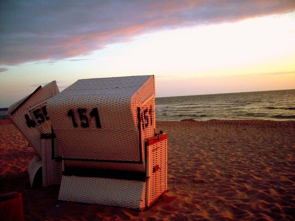 Strandkörbe am Strand der Nordseeinsel Sylt bei Sonnenuntergang