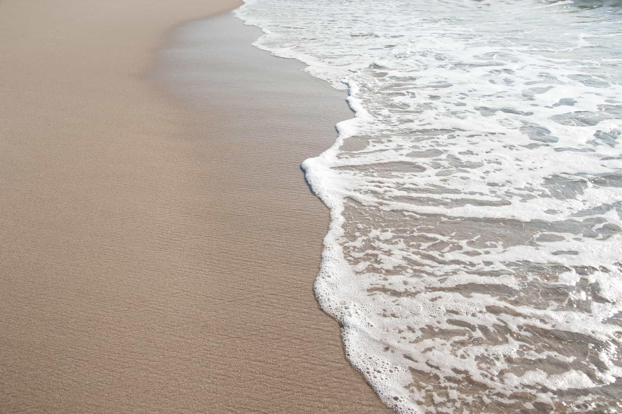 Die Wellen brechen auf dem Strand vor Langeoog. Um dem Abtrieb entgegenzuarbeiten sorgt der NLWKN für die Strandaufspülung.